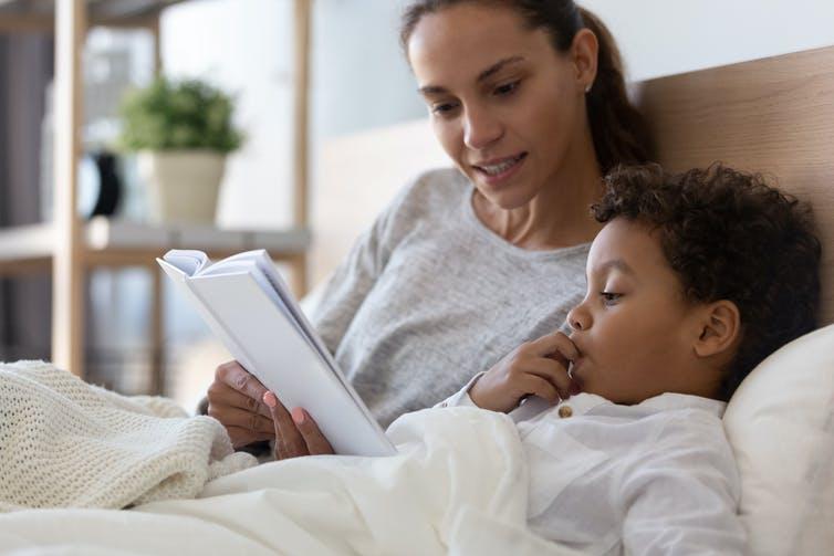 Une femme lit un livre à un enfant, assis sur un lit