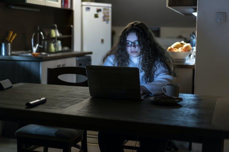 Une jeune fille travaille sur son ordinateur portable tard dans la nuit
