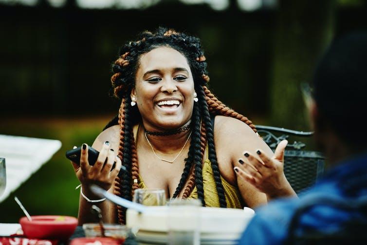 Une femme de forte taille rit et discute avec des amis lors d'une fête dans un jardin