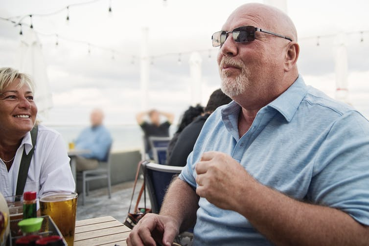 Un homme avec ses amis prenant un repas ensemble sur la terrasse d'un restaurant