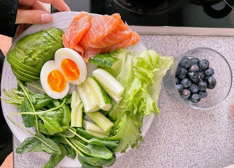 Une assiette de salade, avec œufs, avocat, saumon, etc